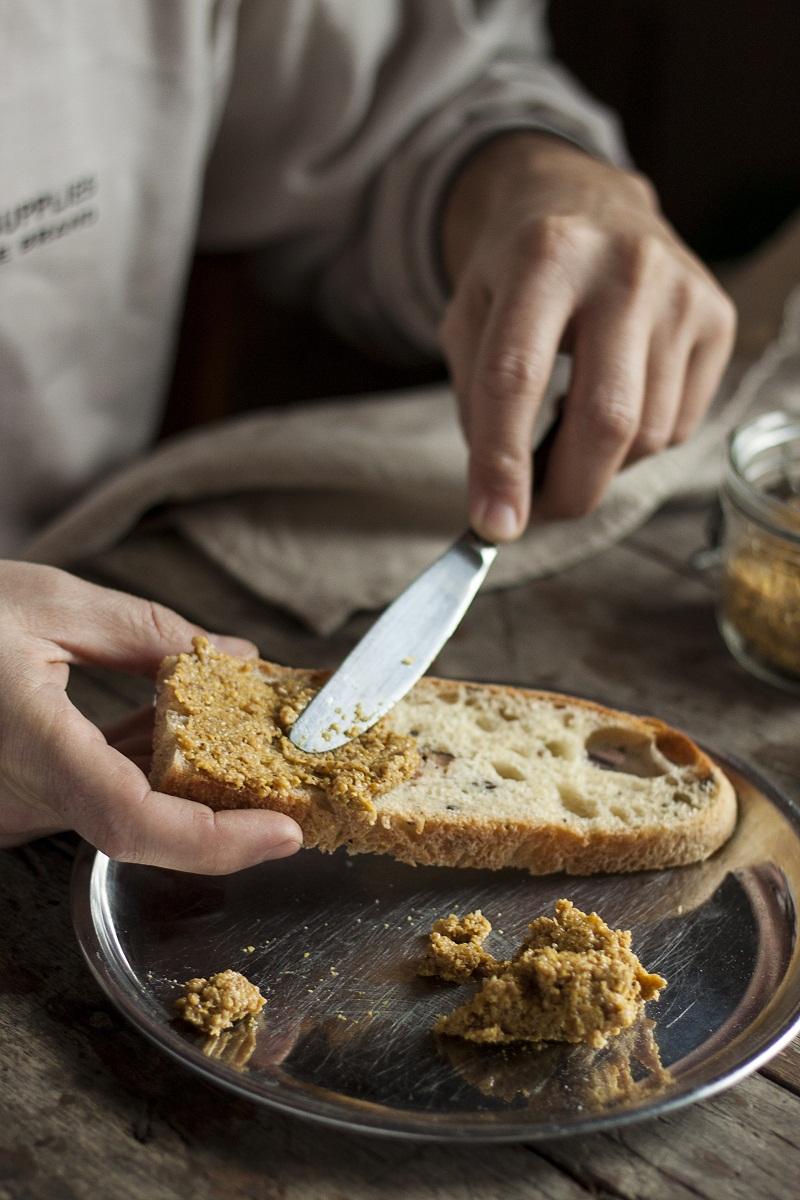 muškarac maže domaći senf na hleb