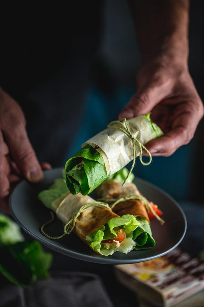 ruka drži zamotuljke sa humusom